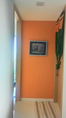 An orange wall in a short corridor to the rooms